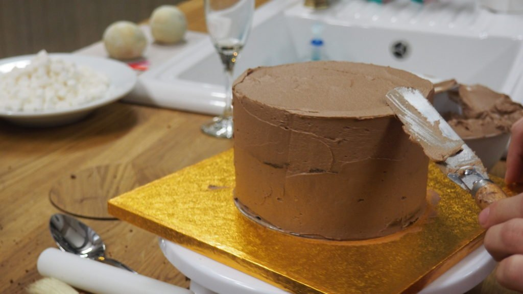 Cake decorating step 2 - After coating the sides of the cake with butter cream, cover the top evenly with butter cream